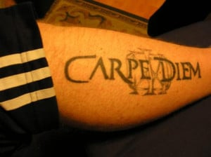 Latin quote tattoo across the forearm in bold black text.