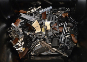 pile of handguns are placed in a trash bin after they were ...