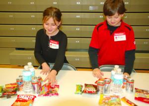 Sarah Isom-Wright (left) and Myles Daugherty arrange snacks for people ...
