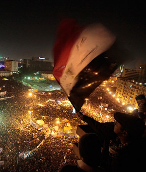An Egyptian waves the national flag as he and others watch thousands ...