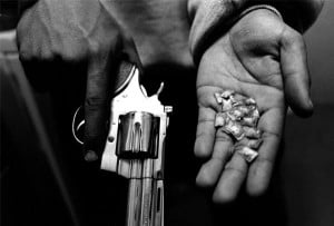 gangster holds the tools of his trade: a gun and dime bags of crack ...