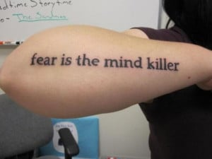 Text tattoo on the arm, quote from Dune: