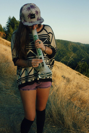 420 girl taking a big bong hit outside while walking in a field next ...
