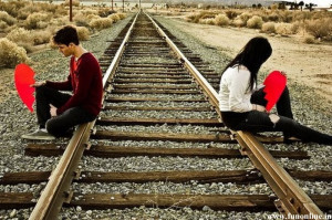 Couple with broken hearts sitting on a track