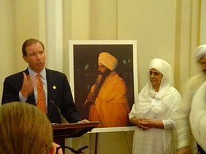 Congressman Tom Udall with Singh's widow, Bibiji. Singh is depicted in ...