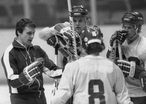coach of the U.S. Olympic hockey team, chats with members of his team ...