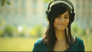 Attractive brunette young adult woman listens music on headphones ...