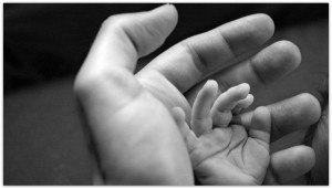 Father holding his baby hand.