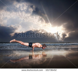 ... man on the beach near the ocean at dramatic sunset sky - stock photo