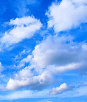Cumulus clouds in blue sky under higher layer of cirrus clouds.