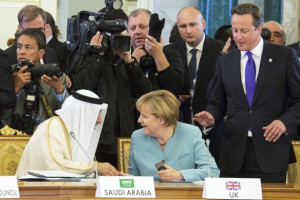 Merkel sits on the place of Britain's Prime Minister Cameron ...