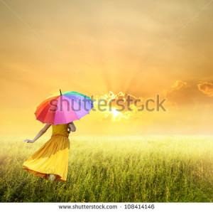 Beautiful woman holding multicolored umbrella in green grass field and ...