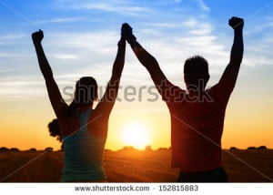 Successful couple of young athletes raising arms to golden summer ...