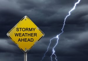 Stormy weather ahead sign with lightning bolt beside it.