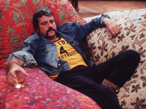 Oliver Reed, sporting a handle-bar moustache, relaxing with a drink ...