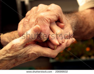 Elderly couple holding hands with love
