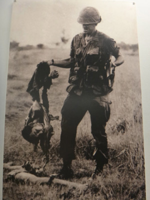 soldier holding the shredded remains of a viet cong soldier