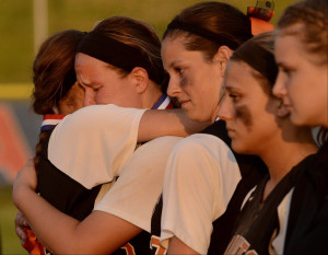 St. Charles East pitcher Haley Beno, center, is consoled by teammates ...