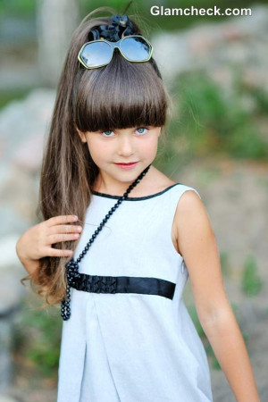 Lovely little girl with funny hair style of the two tails is holding a ...