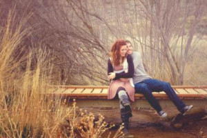 Young couple laugh together sitting on bridge - Anna Gorin/ Moment ...