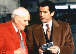 Desmond Llewelyn as Q shows Pierce Brosnan the Quartermaster a