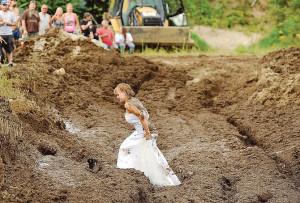 Lucretia (Blais) Gould walks through the mud run pit in her wedding ...