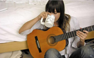 Cat Power sipping her coffee as she plays her guitar