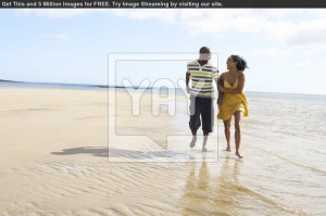 Romantic Young Couple Walking Along Shoreline Of Beach Holding Hands ...