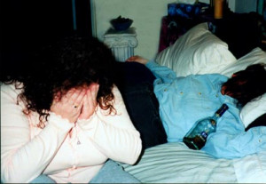 woman sitting on the edge of a bed with her head in her hands nextto ...
