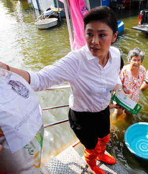 Thailand's Prime Minister Yingluck Shinawatra distributes food to ...