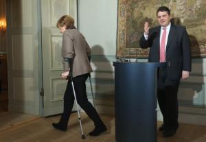 Sigmar Gabriel German Chancellor Angela Merkel walking with crutches