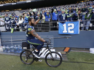 Seattle Seahawks defensive end Michael Bennett (72) rides a bicycle ...