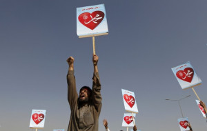 An Afghan protester shouts while holding a sign during a peaceful ...