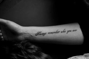 "Always remember who you are"" quote tattoo on girls arm"