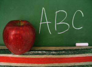 Apple sitting on the ledge of a blackboard