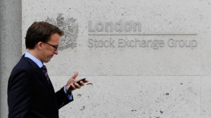 man walks past the London Stock Exchange in central London