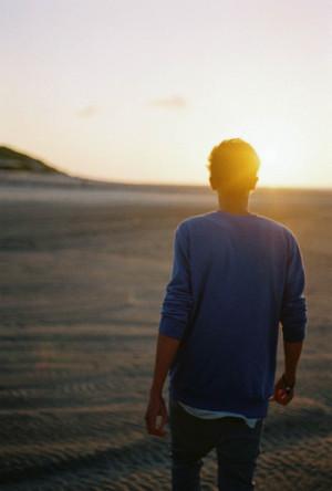 夕阳下,一对情侣手挽着手坐在花坛边看夕阳