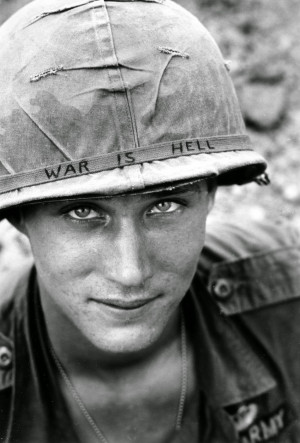 """An American soldier wears a hand lettered """"War Is Hell"""" slogan on ..."""