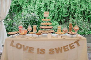 """Decorate your sweet table with a """"Love is Sweet"""" banner."""
