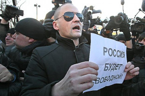 Sergei Udaltsov an opposition leader holds a paper with a sign