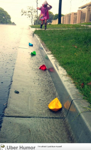 My daughter chasing paper boats in the rain.
