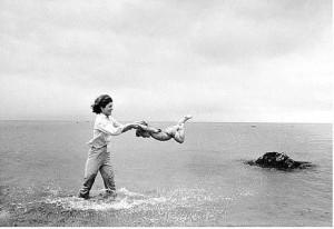 Mark Shaw, Jacqueline Kennedy swinging Caroline in surf, Hyannis Port ...