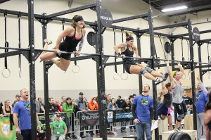 Erin Taylor, left, Jess Core's partner, competes in Bar Muscle Ups ...