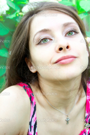 Portrait of beautiful girl with green eyes on flowers background ...