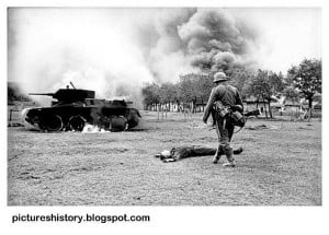 Russia. A German soldier walks over to inspect a destroyed Soviet tank