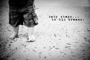 ... walking on the beach with a quote that says baby steps to big dreams