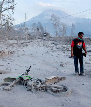 villager stands in front of Mount Merapi, near his motorcycle ...