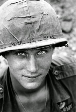 "An American soldier wears a hand lettered ""War Is Hell"" slogan on ..."