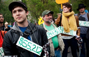 Occupy Wall Street demonstrators displaying their student loan debts ...