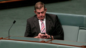 Peter Slipper checks his messages on the House of Representatives back